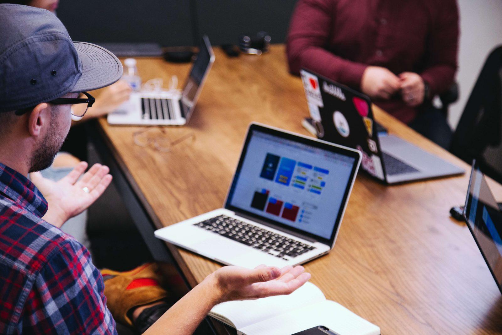 Junger Mann mit Cap sitzt am Meeting Tisch und trägt seine Ergebnisse vor